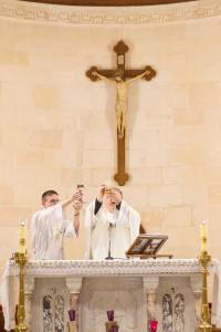 Fr. Bob and Deacon Cronin, elevate the chalice and host in the Church of the workshop of St. Joseph, Nazareth