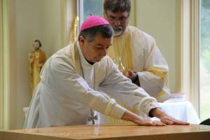 Bishop Medley spreads the Sacred Chrism Oil across the mensa of the Altar.