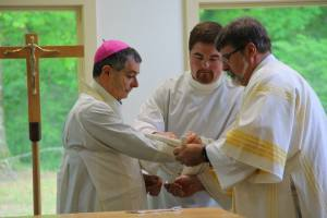 Deacon Matthew and I assist the Bishop in binding his sleeves and placing a gremial on him.